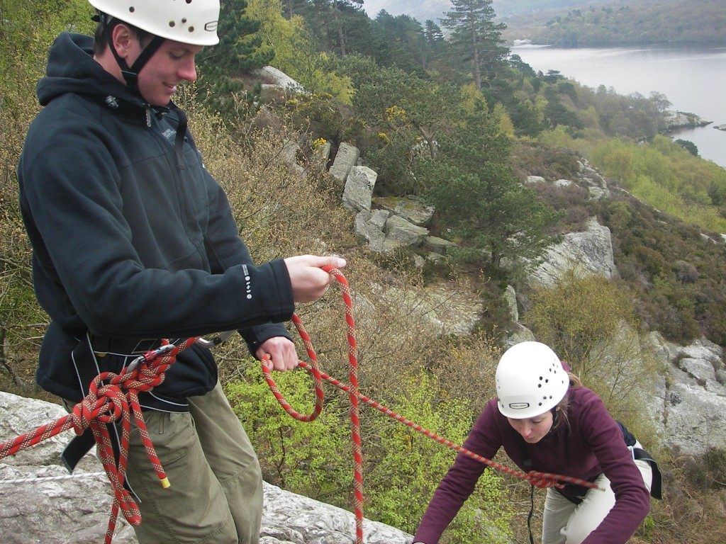 Climber reaching top of climb